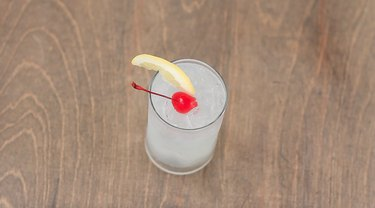 tom collins garnished with lemon wedge and cherry