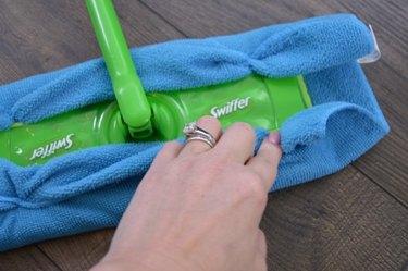 Attach microfiber cloth to Swiffer mop.