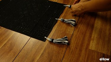 Attaching tassels to DIY mudcloth-inspired wall hanging.