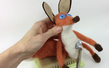 Female hands holding a needle felted fox and mini iron