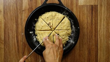 Cutting a round of low-carb, gluten-free scone dough into 8 wedges.