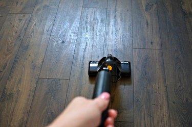 Vacuum wood floors to remove dirt and debris.