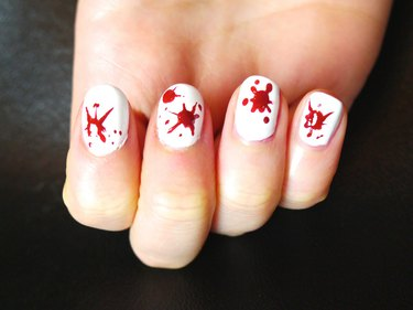 Large, single splats of blood on white nails.