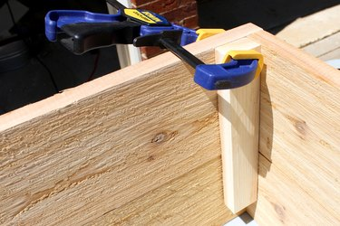 """using 2 clamps attach a 9"""" wood slat   how to make an elevated planter box"""