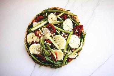 Asparagus, Sun-dried Tomato, Pesto and Arugula Pizza ready for baking.