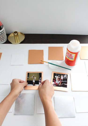 Person gluing photos to metal squares