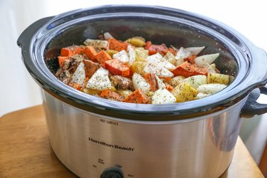 All pot roast ingredients in a slow cooker