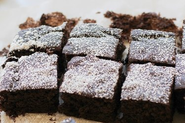 Six black bean brownies, dusted with powdered sugar..