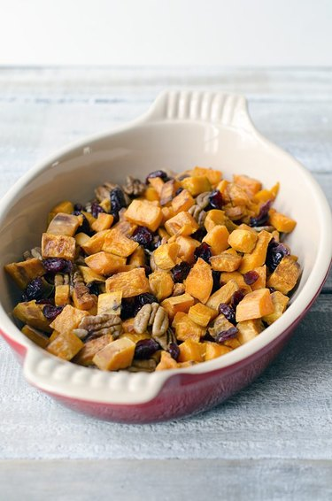 A casserole dish of roasted sweet potatoes, cranberries and pecans.