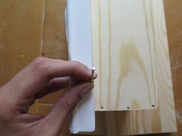 Nail the frame to the wooden box.