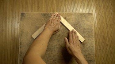 Gluing wood stir sticks to tabletop in herringbone pattern.