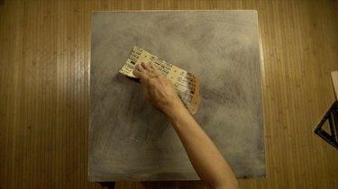 Sanding old tabletop for DIY herringbone pattern tabletop using paint sticks.