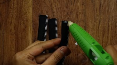 Gluing together three zipper pieces of equal lengths to create a braided zipper bracelet.