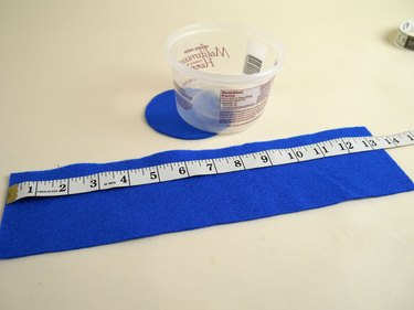 A plastic tub with a blue felt rectangle and circle matching the measurements of the tub.