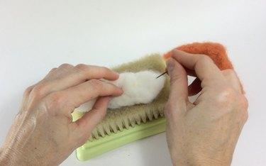 Female hands needle felting white roving on a felting pad