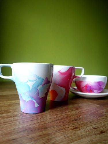 DIY Nail polish marbled mugs on table.