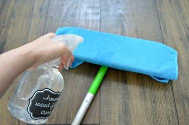 Spray wood floor cleaning solution onto microfiber cloth.
