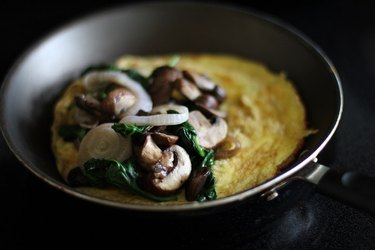 Sauteed onions, mushrooms and spinach placed on one half of the cooked eggs in a skillet.