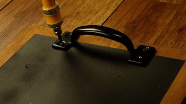 Attaching front-mounting cabinet pulls for DIY chalkboard serving tray.