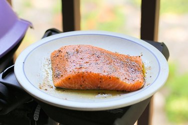 Salmon on a plate next to a grill