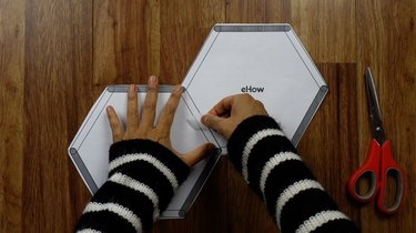Taping templates to make popsicle stick hexagon shelves.
