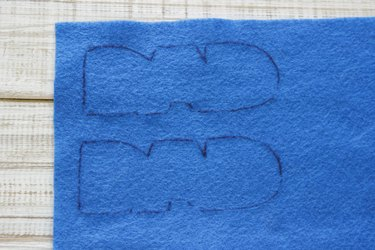 """""""DAD"""" design traced one above the other onto blue felt."""