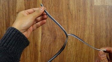 Pulling zipper teeth apart to separate