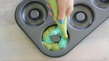 Piping green and blue donut batter into pan