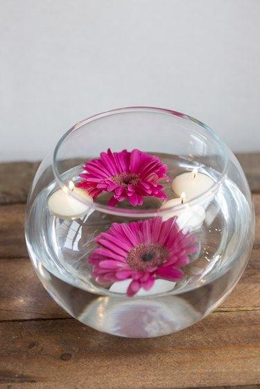 Large vase with floating candles and flowers.