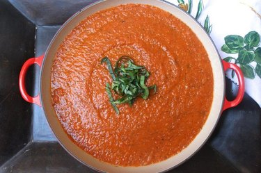 A large pot of tomato sauce with chopped basil.