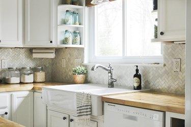 Herringbone marble tile backsplash in a white kitchen