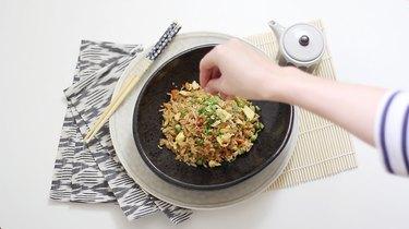 garnishing fried rice with sesame seeds