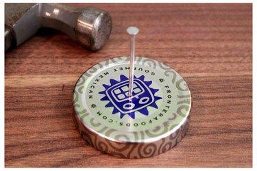 Punching holes in jar lid.