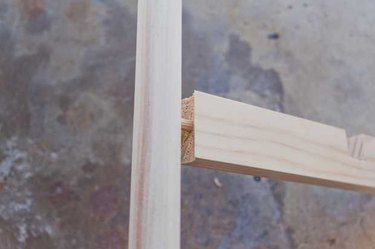 Inserting a dowel into the cross brace, then fitting the cross brace into the hole in the stand