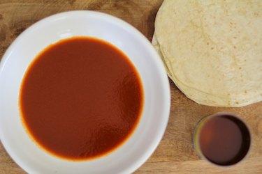 Bowl of enchilada sauce next to a stack of flour tortillas.