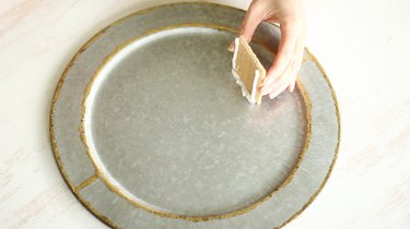 Sticking side piece into icing on plate