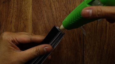 Applying glue to unfinished end of braided zipper bracelet.
