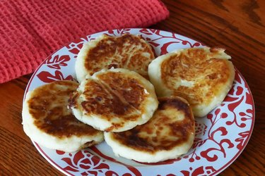 Potato pancakes on red and white plate.