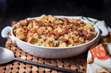 A white casserole dish full of corn bread and bacon stuffing