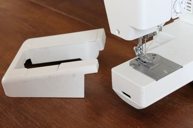 Remove part of the sewing machine bed and use the sleeve arm.