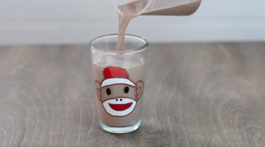 Fill sock monkey glass with chocolate milk