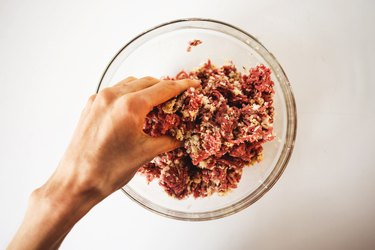 Using hands to combine the ingredients in a bowl.