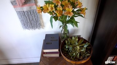 A vase of real flowers next to an arrangement of faux succulents.