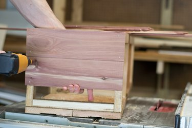 Secure the cedar planks to the side of the interior support - starting with the sides.