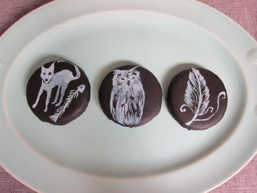 Cookies painted with a cat, owl and feather