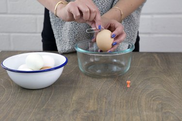 Using straightened paperclip to mix egg white and yolk.
