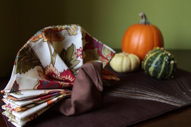 Napkins folded into the shape of a turkey on a tabletop with gourds.