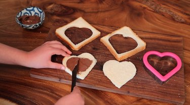 spreading chocolate filling onto bread