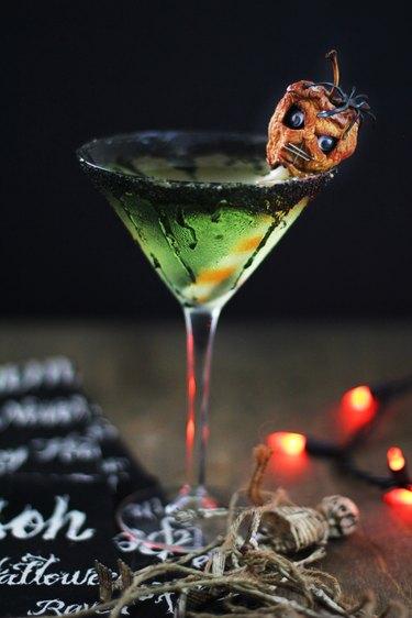 green caramel apple martini garnished with shrunken head