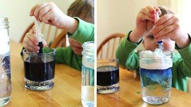 Child adding coloring to shaving cream cloud